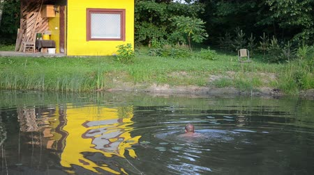 sulky : Man swim in dirty little garden pond water near bath house.