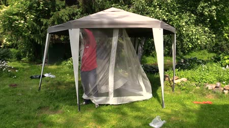 komary : Man attach protective tent bower net in garden. Protection from sun rain and mosquitos insects in nature.