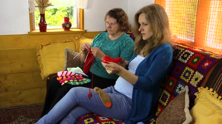 příze : Happy pregnant granddaughter woman spend time knitting with senior old woman.