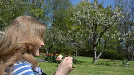 ложка : Beautiful woman enjoy eat sweet pie cake piece between colorful blooms in spring garden. Стоковые видеозаписи