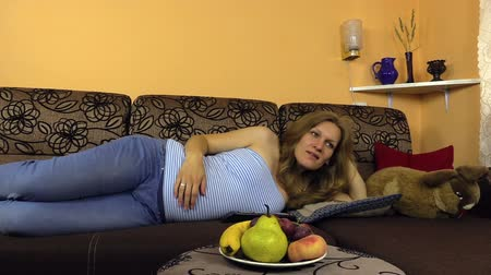 umbigo : nice pregnant woman lying on the couch, palm her belly, pressing buttons on the remote control tv. Shot on Canon XA25. Full HD 1080p. Progressive scan 25fps. Tripod