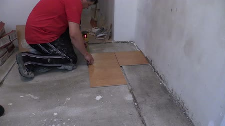urychlit : Bucket full of cement adhesive glue and handyman man measure tiles on floor. Construction works. Zoom out shot on Canon XA25. Full HD 1080p. Progressive scan 25fps. Tripod. Dostupné videozáznamy