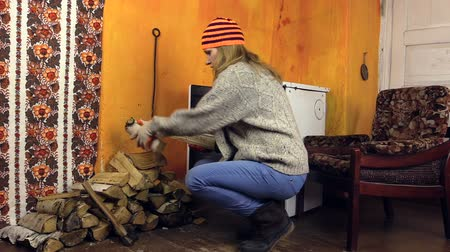 günlüğü :   girl with thick woolen sweater and orange hat bring armful firewood, sit in an armchair and bask hands of furnace. Shot on Canon XA25. Full HD 1080p. Progressive scan 25fps. Tripod  Stok Video