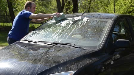 gąbka : Young man carefully wash his favourite car windscreen and roof on open air.