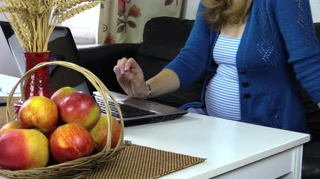 apple computers : Pregnant business woman talk mobile phone and work with notebook on white desk with apple fruits at home.