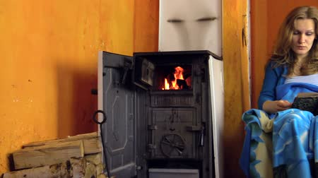 fogão : woman read book sitting on armchair at home on cold winter day and fire flame burn in rural wooden stove. Zoom in shot on Canon XA25. Full HD 1080p. Progressive scan 25fps. Tripod.