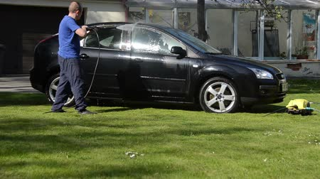 lavagem : VILNIUS,LITHUANIA - APRIL 26, 2014: Worker man wash Ford Focus car automobile with strong water jet on garden lawn in summer on April 26, 2014 in Vilnius, Lithuania. Vídeos