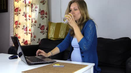 усталый : tired pregnant woman looking for information on your computer in home, freshen up with fresh orange juice Стоковые видеозаписи