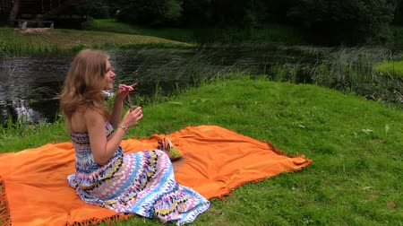 giydirmek : blonde smiling woman with long dress drink lemonade on orange rug near stream on sunny summer green park. Full HD 1080p. Progressive scan 25fps. Tripod
