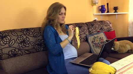 banany : pregnant young woman chatting on internet, spending time on laptop, eat fresh banana, relaxing with laptop at home. Approach shot. Full HD 1080p. Progressive scan 25fps. Monopod