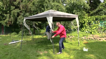 komary : People fix garden tent bower long metal legs. Protection from sun rain and mosquitos insect in nature. Full HD 1080p. Progressive scan 25fps. Tripod.