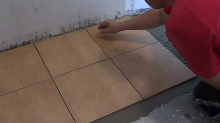 устанавливать : Handyman lay floor tiles at home. Closeup shot. Full HD 1080p. Progressive scan 25fps. Tripod.