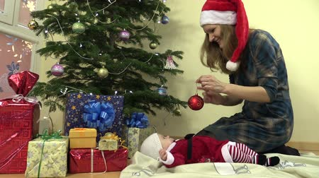 toy : Cheerful woman with Santa hat hang christmas tree toy ball. Infant baby daughter in christmas festive dress. Presents gifts. Sliding forward shot on Canon XA25. Full HD 1080p. Dolly camera movement.