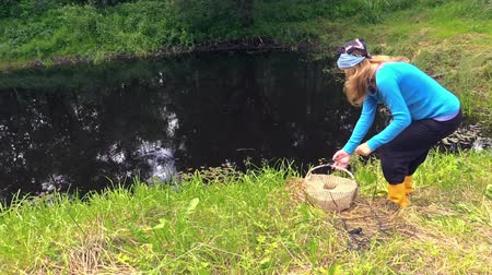csizma : girl throw the old fishing bag with net in the pond.