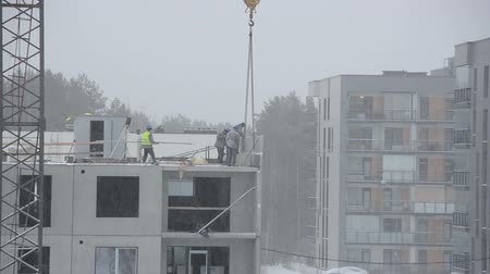 kar fırtınası : Snow falling and construction site workers build house in dramatic weather conditions in winter.