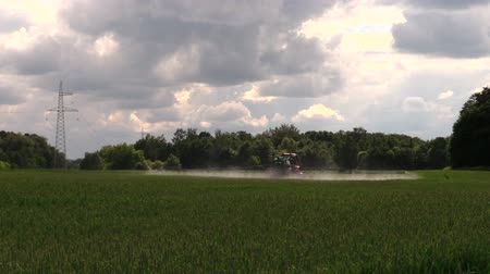 trator : farm tractor spraying wheat field with sprayer herbicides and pesticides. Seasonal village work. Blue cloudy sky in background. Shot. Full HD 1080p. Progressive scan 25fps. Tripod