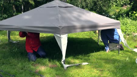 komary : Father and son fix tent cloth roof on garden bower arbour construction. Protection from sun rain and mosquitos insect. Zoom in Full HD 1080p. Progressive scan 25fps. Tripod.