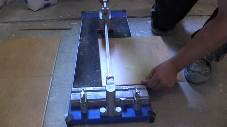 řezačka : worker hand using tile cutter at home repair renovation work. Shot. Full HD 1080p. Progressive scan 25fps. Tripod.