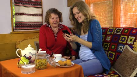 gerações : granddaughter and grandmother sit at table beautifully covered with tea and watch photo on smartphone two generation weekend time. Full HD 1080p. Progressive scan 25fps. Tripod