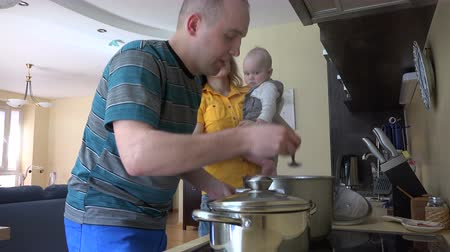 cooking pots : Man husband cooking in kitchen and woman wife with curious infant baby in hands taste meal dish from man hands. Family time together. Vapor steam rise from pot. Static shot. 4K UHD video clip.