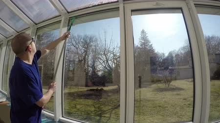 temizleme maddesi : worker man with sun glasses spray liquid cleaner on window and wipe dirt from glass with washer squeegee tool in front of sun. Cleaning conservatory windows in spring. 4K UHD wide angle shot.
