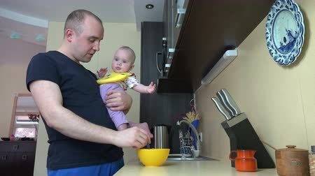 держит : Careful father man feeding his baby daughter with spoon holding in hands in kitchen at home. Infant girl eating food mash. Static shot. 4K UHD video clip. Стоковые видеозаписи