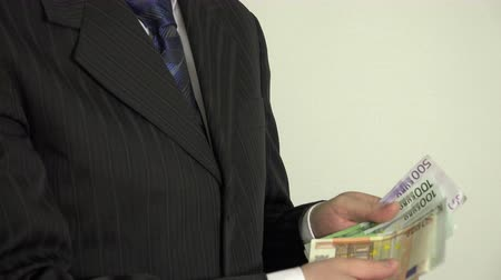 venality : Successful salesman man hands count money cash euro banknotes on white background. Businessman in suit. Closeup shot. 4K UHD video clip.