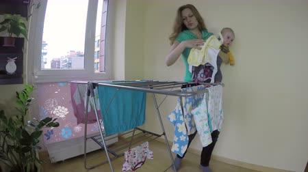 домохозяйка : Mother woman with newborn baby on her hands pick up dry laundry at home. Wide angle shot. 4K UHD.