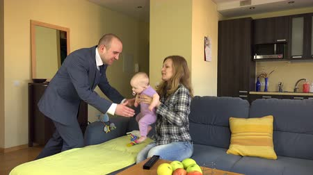 взятие : businessman father return from work take his baby on hands and pay cash euro money babysitter nanny for caring newborn. 4K UHD video clip.