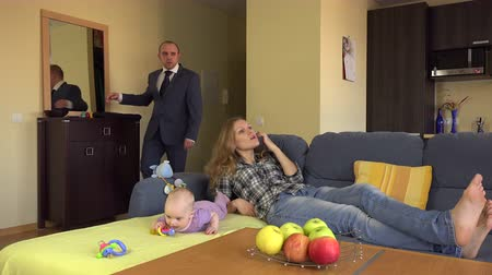 sulk : Relaxed nanny mother lay on sofa near newborn baby. Angry father man in suit return from work and take baby on hands. 4K UHD video clip.
