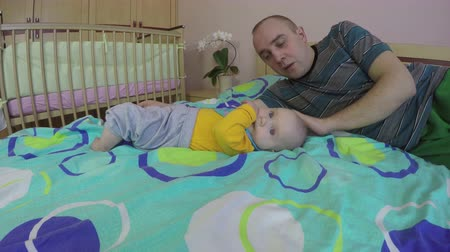 novorozený : Tired father man wake up and care his cute newborn baby daughter girl move near him. Fatherhood bother. 4K UHD wide angle shot. Dostupné videozáznamy