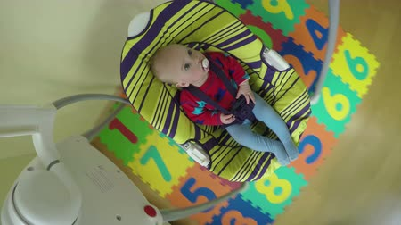 nipple : baby boy or girl sway in special colorful swing at home. Infant child sleep time. Camera mounted on top of swing. Wide angle shot. 4K UHD video.