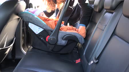 ülés : Loving mother woman put baby safety chair with infant child on back car seat and fasten with safety belt. Safe baby transportation inside automobile. 4K UHD video clip.