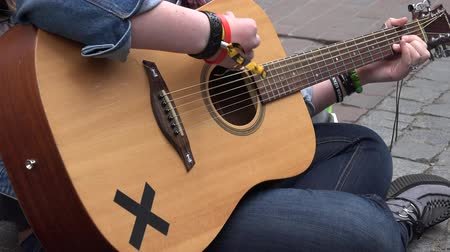 music show : Woman girl hands play with acoustic guitar musical instrument on street pavement. Street music day. Static shot. 4K