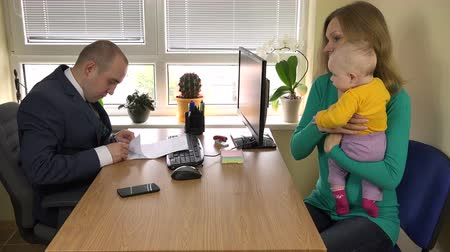 daň : Woman with newborn baby on her hands take loan and sign documents with bank officer. Government clerk in suit look at documents. Financial tax adviser at cosy office. 4K UHD video clip. Dostupné videozáznamy