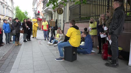 способствовать : VILNIUS, LITHUANIA - MAY 16: Man contribute money for children with cancer disease fund on May 16, 2015 in Vilnius, Lithuania. Young people group sing. Street music day. Panorama shot. 4K Стоковые видеозаписи