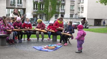 plucked : VILNIUS, LITHUANIA - MAY 16: children play with zither Lithuanian plucked string musical instrument and teacher with guitar on May 16, 2015 in Vilnius, Lithuania. 4K UHD video clip. Panorama view.