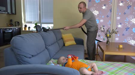 чистый : father man hoover dust from sofa near baby daughter. home clean and child care. Multitasking. 4K UHD video clip.