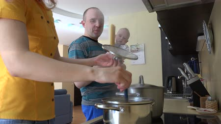cooking pots : Father man with baby in hands and mother woman put spaghetti in steamy pot. Happy family cook in kitchen. Static shot. 4K UHD video clip.