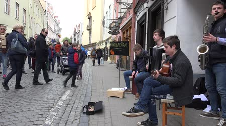 serenade : VILNIUS, LITHUANIA - MAY 16: group of young guys student play different musical instruments and earning money on the street on May 16, 2015 in Vilnius, Lithuania.  4K UHD video clip.
