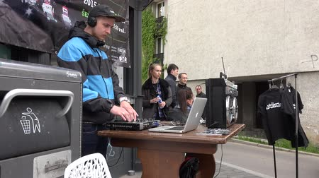 waggle : VILNIUS, LITHUANIA - MAY 16: Dj with mixer play house progressive electro music near trash container in street on May 16, 2015 in Vilnius, Lithuania. People tourists walking. Street music day. 4K