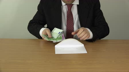 bancário : man in suit prepare envelope with money for bribe. Hands take cash euro banknotes from jacket pocket and put into envelope on white background. Corruption concept. Closeup shot. 4K UHD video clip. Vídeos