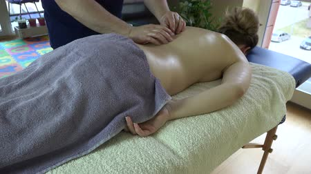gyógyász : Massage therapist is treating female client on table in apartment. Tired housewife enjoy releasing back massage. 4K UHD video clip.