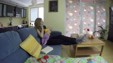 angrily : Mother sit on sofa and still little child in her arms, answer angrily the phone. 4K UHD wide angle shot.
