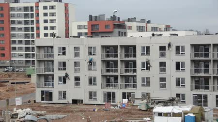 blocks of flats : Construction workers insulate new residential house wall stitch joints hanging on rope. New block building insulation. Stock Footage
