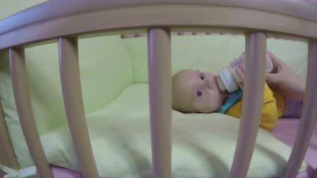 descontente : mother hand feed bottle milk small hungry baby girl in bed in living room. Walking camera shot. 4K UHD wide angle shot. Vídeos