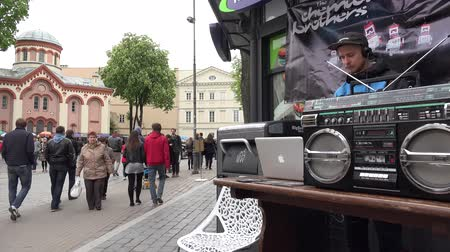 waggle : VILNIUS, LITHUANIA - MAY 16: DJ man with hat and beard play house progressive music near trash container in street on May 16, 2015 in Vilnius, Lithuania. People tourists walking. Street music day. 4K Stock Footage