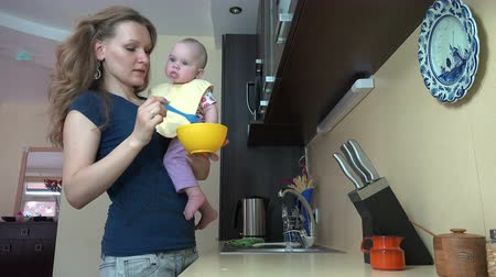 babycare : happy young woman feed little baby daughter with spoon in kitchen. Motherhood and baby care at home. Static tripod shot. 4K UHD video clip.
