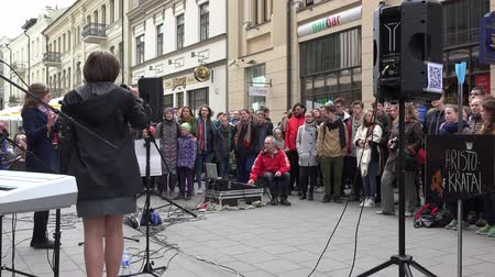 waggle : VILNIUS, LITHUANIA - MAY 16: street musician band with vocalist woman sing and play popular music outdoors on May 16, 2015 in Vilnius, Lithuania. Street music day. Static shot. 4K Stock Footage