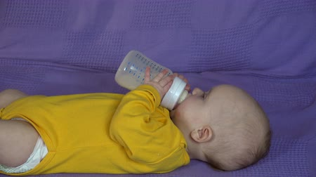 infant formula : baby hold and drink milk from bottle himself. Alone cute newborn girl or boy with yellow cloth in bed. Pretty infant boy drinking milk from bottle. 4K UHD closeup shot. Stock Footage